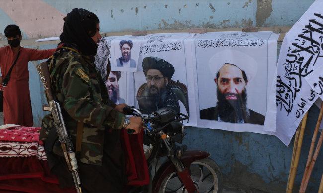 8월 25일 아프가니스탄 카불에서 한 탈레반 병사가 탈레반 깃발과 지도자들 사진을 바라보고 있다. [AP=뉴시스]