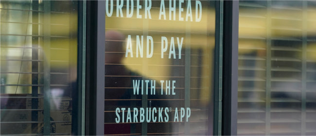 """2020년 10월 미국 시애틀 남부에 있는 한 스타벅스 커피 매장 창문에 """"미리 주문하고 스타벅스 앱으로 결제하세요""""라는 안내문이 붙어 있다. 스타벅스는 앱 선결제 시스템 '사이렌오더'를 통해 매년 막대한 충전금을 확보하고 있다. [AP=뉴시스]"""