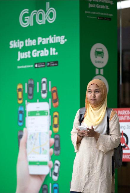 말레이시아 쿠알라룸푸르 한 쇼핑몰 앞에서 '그랩' 차량을 기다리는 여성. 말레이시아에서 택시 호출 애플리케이션으로 시작한 그랩은 금융 분야로까지 사업을 확장하며 동남아 전역에서 사랑받는 '슈퍼 앱'이 됐다. [AP=뉴시스]
