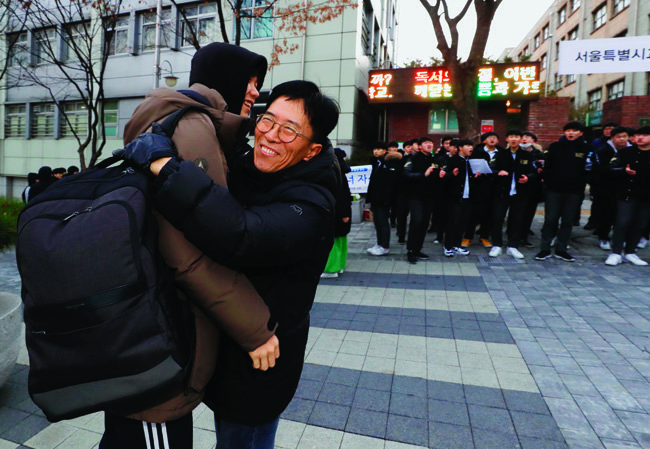 한 교사가 양재고 고사장 앞에서 기다리다 제자들을 한 명씩 포옹하며 응원하고 있다.