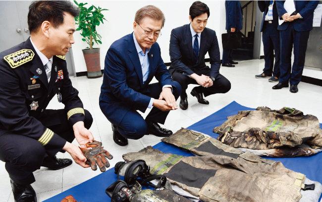 문재인 대통령(가운데)이 지난해 6월 서울 용산소방서를 방문해 소방관들이 사용했던 장비를 살펴보고 있다. [동아일보]