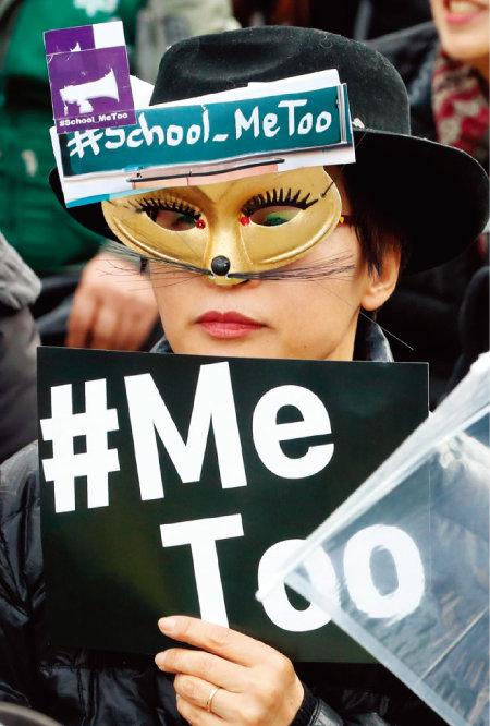 3월 8일 오후 서울 종로구 광화문광장에서 열린 3·8 세계 여성의 날 전국여성노동자대회에서 가면을 쓴 한 참가자가 미투 손팻말을 들고 있다. [뉴시스]