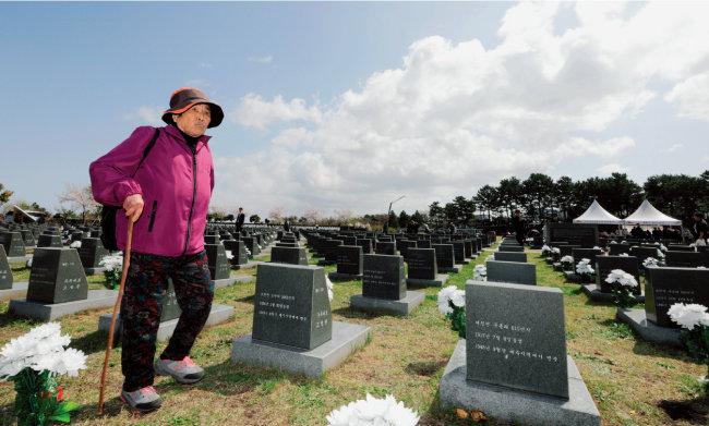 행방불명된 희생자들의 묘비 사이로 유가족 할머니가 걸어가고 있다.