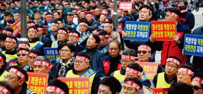 3월 18일 서울 광화문 동화면세점 앞에서 열린 '전국의사대표자회의' 참석자들이 국민건강보험 보장성 강화 정책(문재인 케어)에 반대한다는 내용의 손팻말을 들고 있다. [동아일보]