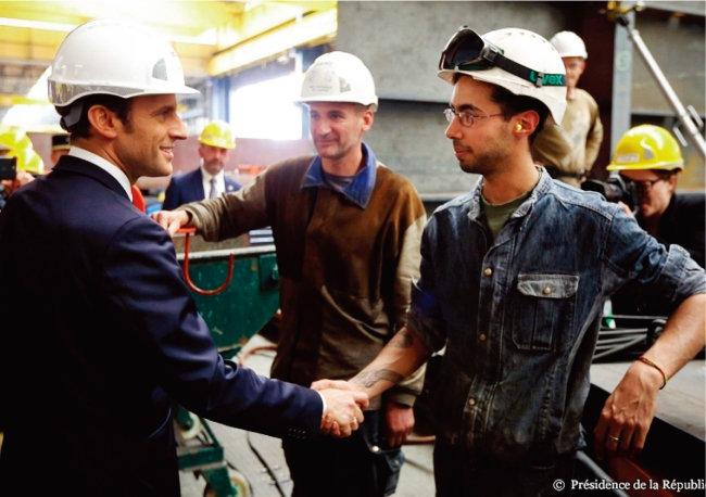 에마뉘엘 마크롱 프랑스 대통령(왼쪽)이 한 공장을 방문해 노동자와 악수하고 있다. [엘리제궁 온라인 사이트]