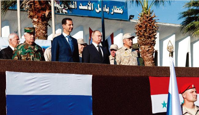 블라디미르 푸틴 러시아 대통령(가운데)과 바샤르 알아사드 시리아 대통령(왼쪽에서 두 번째)이 시리아 내 흐메이님 러시아 공군기지에서 양국 군을 사열하고 있다. [러시아 크렘린궁 온라인 사이트]