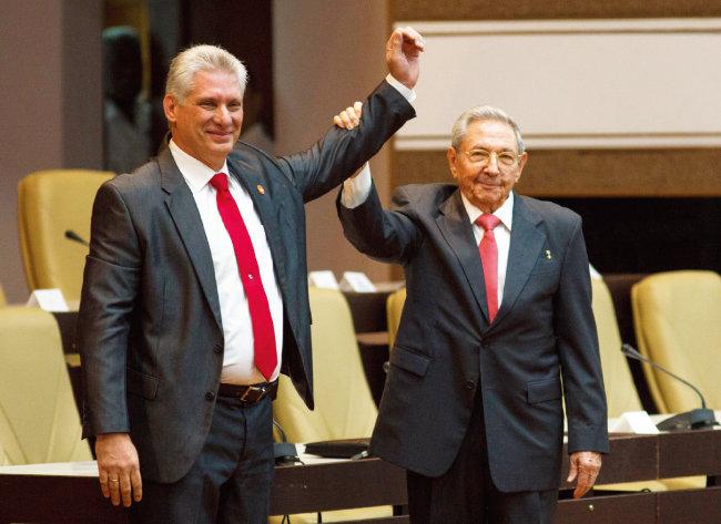 미겔 디아스카넬 쿠바 새 국가평의회 의장(왼쪽)이 4월 19일(현지시각) 수도 아바나 국가평의회에서 라울 카스트로 전 의장과 함께 손을 들어 보이고 있다. [뉴시스]