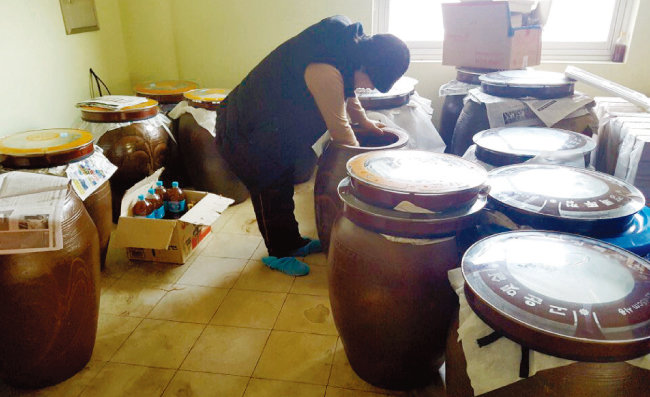 와송식초 숙성실에서 항아리 뚜껑을 열어 식초 상태를 확인하고 있는 이광자 대표. [사진 제공·이광자]