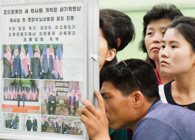 """북한 주민들이 6월 13일 평양 지하철역에서 김정은 국무위원장과 도널드 트럼프 미국 대통령의 정상회담 소식을 보도한 '노동신문'을 보고 있다. 노동신문은 13일자에서 """"조미관계의 새 역사를 개척한 세기적 만남""""이라며 12일 정상회담 소식을 4개 면에 걸쳐 보도했다. [평양=AP 뉴시스]"""