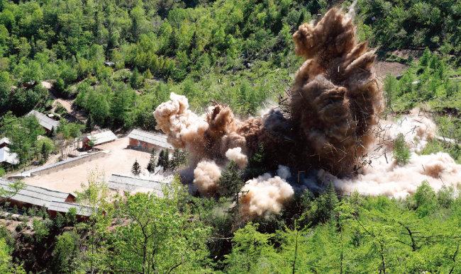 5월 24일 함북 길주군 풍계리 핵실험장의 핵실험 관리 지휘소 시설이 폭파되며 목조 자재와 돌멩이들이 하늘로 솟구치고 있다. 이날 지휘소 시설 7개 동이 폭파됐다. [길주=사진공동취재단]