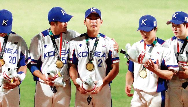 시상식에서 금메달을 목에 걸고 있는 야구대표팀. 하지만 오지환(가운데) 선수 등은 병역면제 논란에 휩싸였다. [뉴시스]