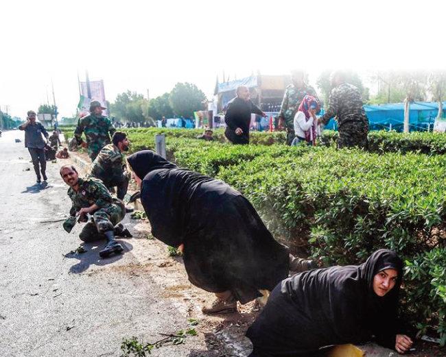 차도르를 두른 이란 여성들도 황급히 화단 뒤로 몸을 숨겼다. [AFP=뉴스]