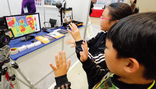 열화상카메라 앞에서 관람객들이 자신의 모습이 어떻게 비치는지 확인하고 있다.