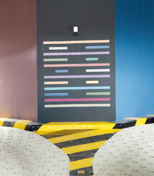 디어스 타워의 입면 형상을 단순화한 그림에 층마다 12가지 색깔을 입힌 로고. 주차장과 유리창 등 건축 도처에 숨어 있다. [지호영 기자]