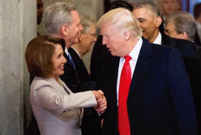 도널드 트럼프 미국 대통령이 취임식 날 낸시 펠로시 민주당 하원 원내대표(왼쪽)와 악수하고 있다. [미국 백악관]