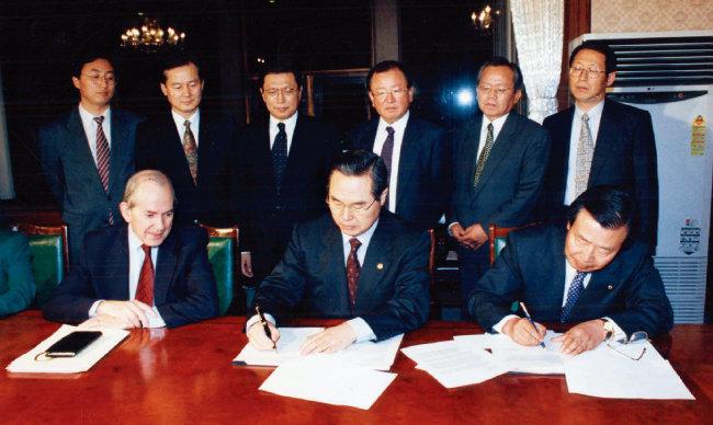 1997년 12월 3일 서울 종로구 정부종합청사(현 정부서울청사)에서 미셸 캉드쉬 국제통화기금 총재(아랫줄 왼쪽)가 지켜보는 가운데 임창열 당시 경제부총리 겸 재정경제원 장관(아랫줄 가운데)이 구제금융 합의서에 서명하고 있다. [동아DB]