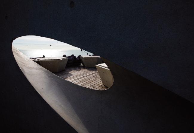 옥상으로 올라가는 목조계단의 난간 역할을 하는 노출콘크리트 구멍 너머로 포착된 3층 옥외 목조 데크의 풍경. [조영철 기자]