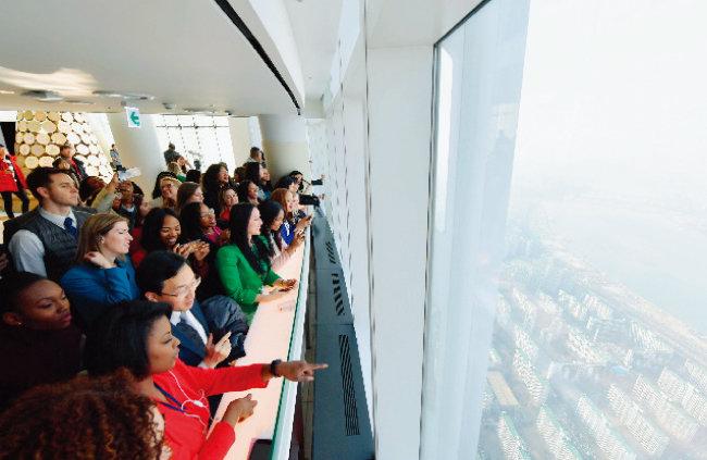 하나님의 교회 제73차 해외성도방문단이 롯데월드타워 서울스카이 전망대에서 한국인 가이드의 설명을 들으며 서울 전경을 구경하고 있다.