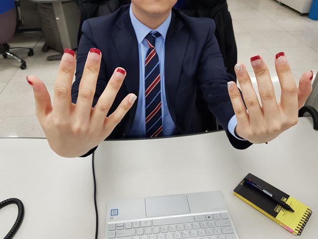 네일아트를 마친 기자의 손. 강한 붉은 색감의 프렌치 네일아트로 새끼손가락에는 큐빅으로 포인트를 줬다.