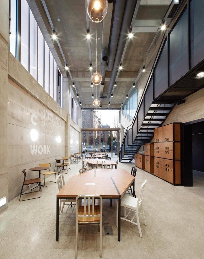 2층 천장을 공유해 시원한 층고를 자랑하는 1층 카페. 높낮이를 달리한 다양한 조명이 눈길을 끈다. [사진 제공 · 진효숙]