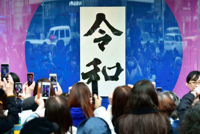 4월 1일 공개된 일본의 새 연호 '레이와'의 대형 서예글씨를 내건 도쿄 한 쇼윈도 앞에 사람들이 모여 사진을 찍고 있다. [AP=뉴시스]
