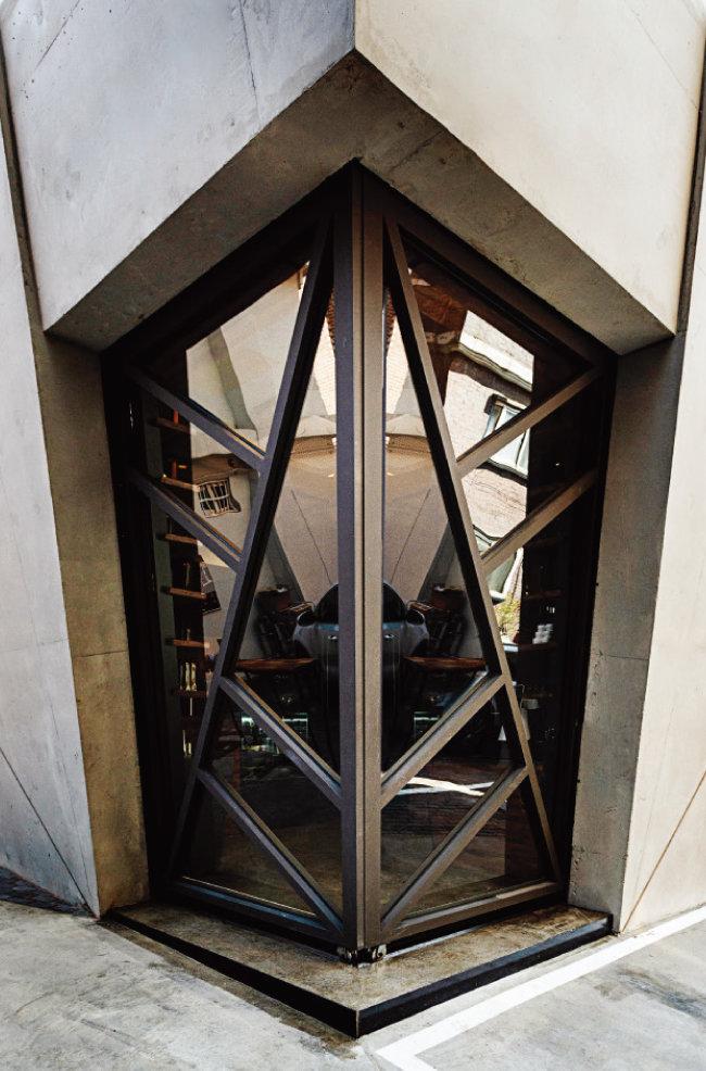 양면 여닫이 슬라이딩 도어로 된 출입구. 꼭짓점과 꼭짓점을 연결하는 기하학적 사선이 공간에 역동감을 부여한다는 건축가 문훈의 미학이 반영돼 있다. [홍태식]