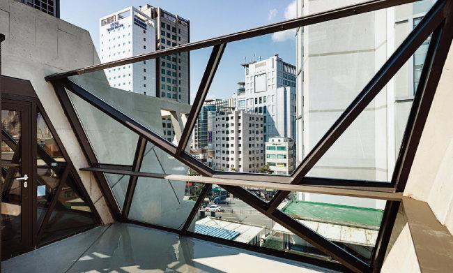 5층에 해당하는 옥상 공간. 쿠킹체험장과 연계해 다용한 용도로 쓸 수 있도록 비워놨다. 1층 출입문의 기하학 무늬를 원용한 커다란 철골 유리창이 눈길을 끈다. [홍태식]