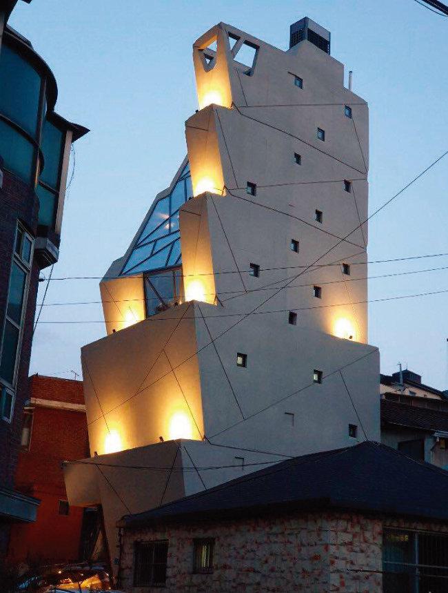 쿠엔즈버킷 도심공장 및 플래그숍의 야경. 위는 넓고 아래는 좁은 버킷(들통) 다섯 개가 층층이 쌓여 있는 형상을 확인할 수 있다. [사진 제공·변용한]