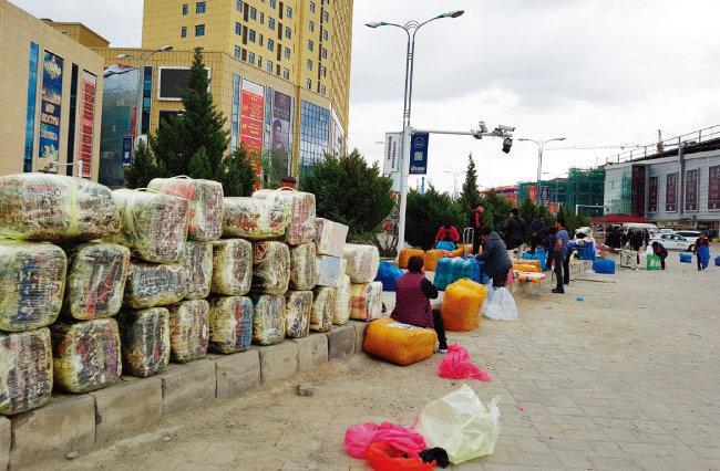중국과 카자흐스탄 접경지역에 위치한 훠얼궈쓰 국제자유무역구에서 중국 제품을 무더기로 구매한 카자흐스탄 상인들이 물품 포장을 마치고 짐 실을 차를 기다리고 있다.
