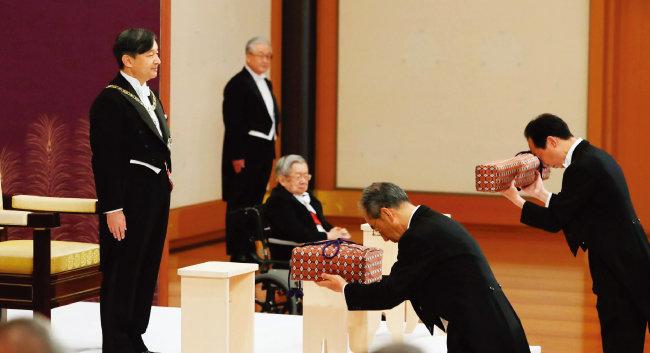 5월 1일 일본  도쿄 고쿄(皇居) 내 마쓰노마에서 열린 즉위식에서 나루히토(왼쪽) 일왕이 왕위 계승의 증명으로 '삼종신기'를 받고 있다. [AP=뉴시스]