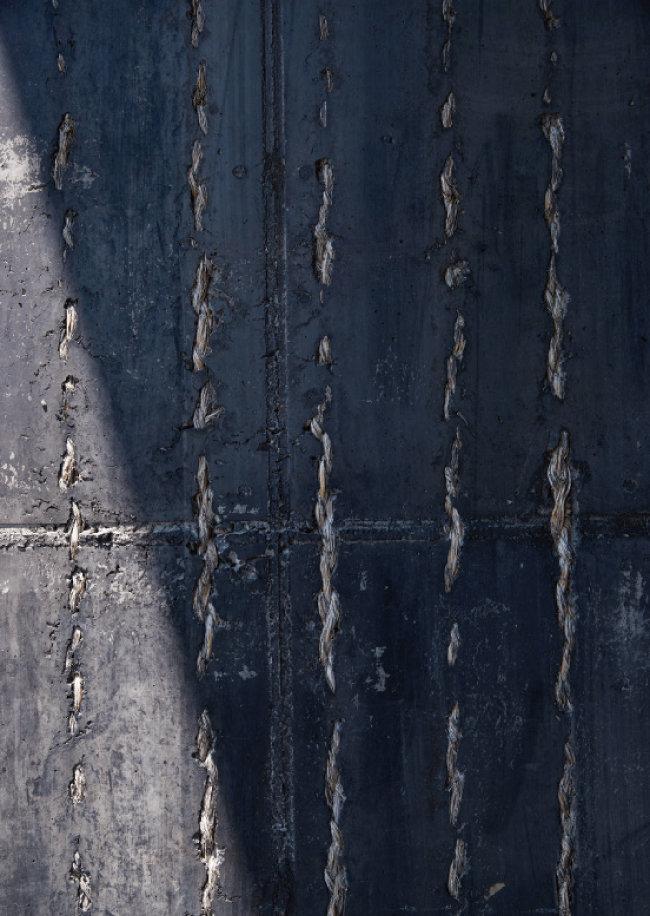 술도가 내부와 천정, 외벽 사진. 태운 볏짚을 섞은 콘크리트로 독특한 잿빛을 빚어낸 복순도가의 외벽에선 볏짚을 꼰 새끼를 포함해 다양한 볏짚의 흔적을 확인할 수 있다. 같은 빛깔을 내고자 인디언잉크 빛의 징크(아연) 천장을 특수 주문해 올렸다. 외부로 술도가의 빛을 흘려보내기 위해 외벽과  천장 사이에 길게 유리창을 설치했다. [홍중식 기자]