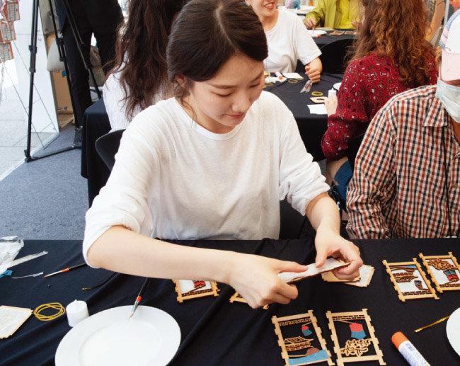 '진주남강유등축제' 홍보 부스에서 참가자들이 작은 크기의 유등을 만들어보고 있다.