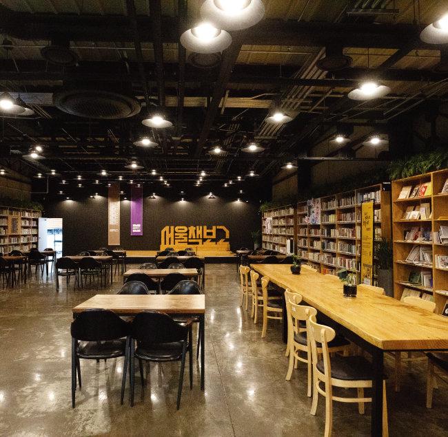대형 철제 서가와 수직축을 이루는 열람실을 겸한 다목적홀. 벽면 서가에 전시된 책들은 독립서점들의 책이다. [지호영 기자]