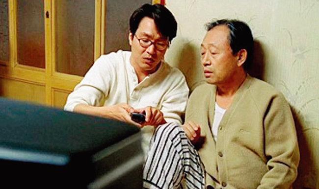 영화 '8월의 크리스마스'에서 아버지(신구 분)에게 리모컨 사용법을 가르쳐주는 아들(한석규 분). [사진 제공 · 우노필름]