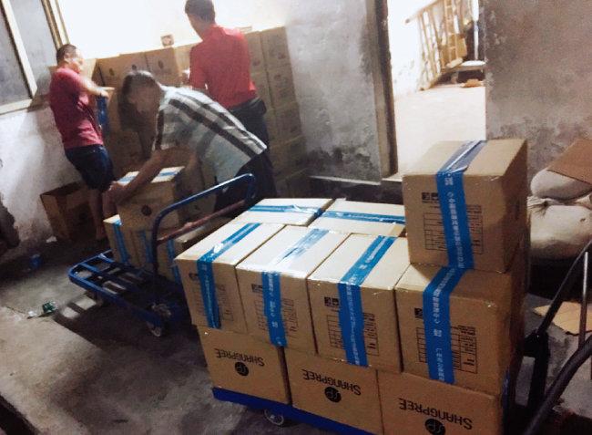 NBST 중국 파트너사인 헬퍼의 감시반원들이 물류창고를 급습해 창고에 쌓여 있는 제품의 진품 여부를 확인하고 있다. [사진 제공 · NBST]