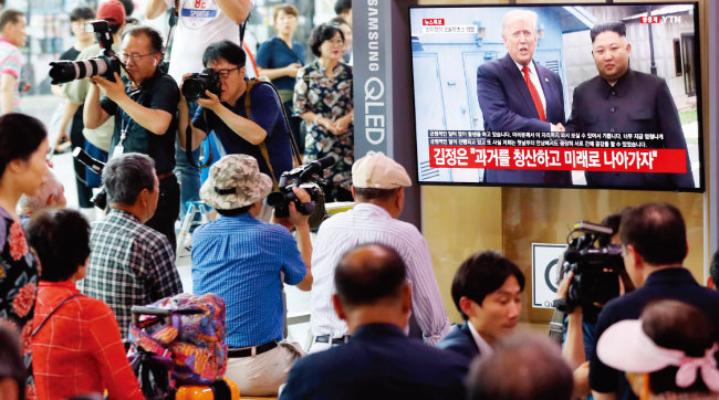 6월 30일 오후 판문점에서 미국과 북한의 두 정상이 만난 모습을 시민들이 서울역사 내 TV로 지켜보고 있다. [뉴시스]