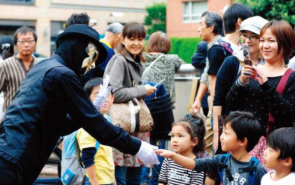 일본 도쿄에서 엄마와 아이들이 퍼포먼스를 펼치는 아티스트와 함께 즐거운 한때를 보내고 있다. [신화=뉴시스]