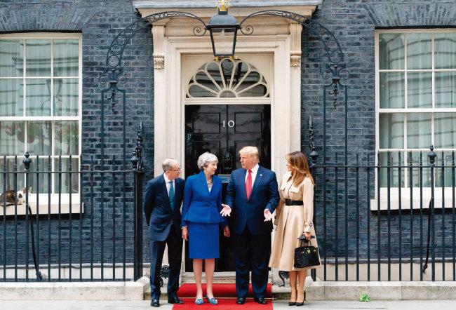 6월 영국을 국빈 방문한 도널드 트럼프 미국 대통령 부부와 테리사 메이 당시 영국 총리 부부가 기념촬영하는 모습을 왼쪽 창문턱에 앉은 '수석수렵보좌관' 래리가 바라보고 있다. [AP=뉴시스]