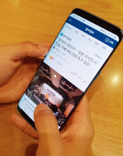 """국내 한일 가정에서 나고 자란 한 20대 청년이 스마트폰으로 한일관계 관련 기사를 보고 있다. '주간동아'에 보낸 글에서 그는 """"일부 극우세력이 아닌 일본인 전체에 대한 선입견은 갖지 않았으면 한다""""고 당부했다. [김우정 기자]"""