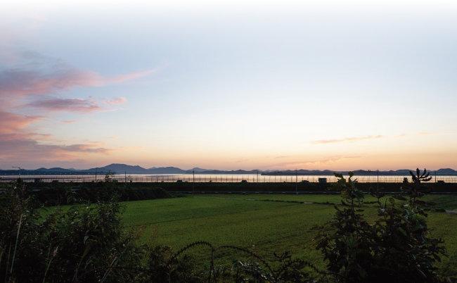 남북 군사분계선 구실을 하는 임진강 철책선 너머 서쪽 하늘로 해가 넘어가고 있다. [지호영 기자]