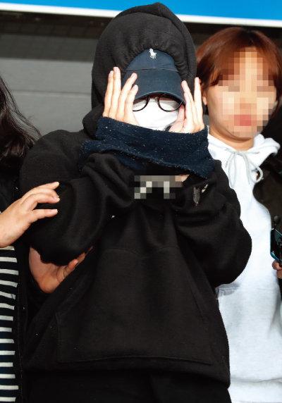 2018년 5월 한 남성의 신체를 불법촬영해 유포한 혐의로 체포된 여성 용의자가 조사 후 서울 마포구 마포경찰서에서 이송되고 있다. [뉴스1]