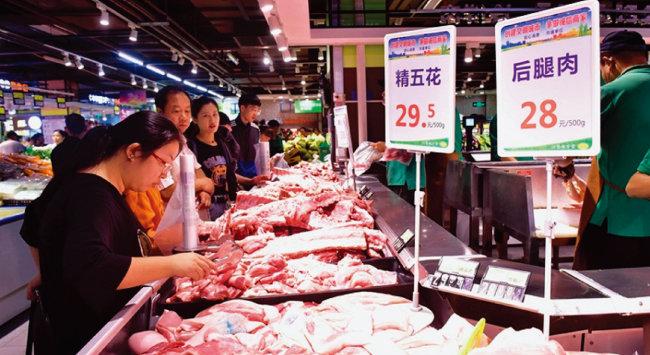 중국인 주부가 시장 정육점에서 돼지고기를 살펴보고 있다. [VCG]