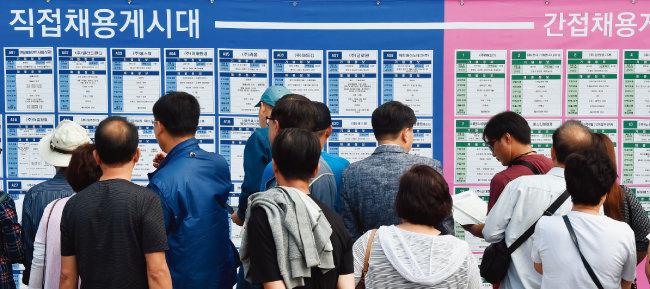 9월 24일 오후 경기 군포시 당정역 야외광장에서 열린 '2019 경기도 중장년 일자리 박람회'에서 구직자들이 채용 게시판을 살펴보고 있다. [뉴시스]