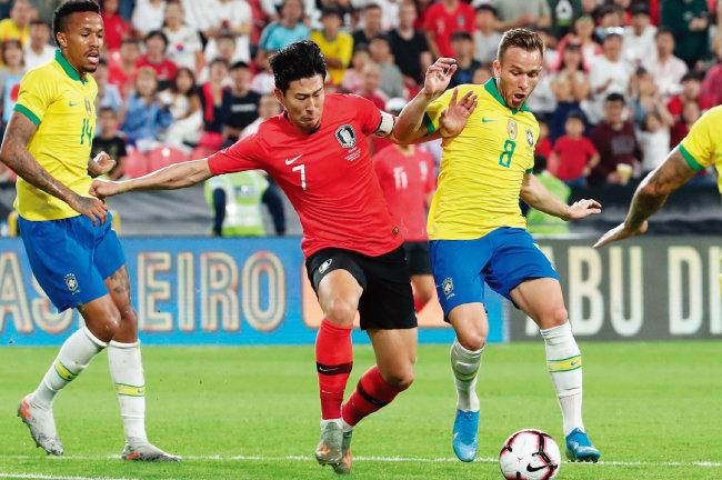 11월 19일 아랍에미리트(UAE) 모하메드 빈 자예드 스타디움에서 열린 축구 국가대표팀 평가전 대한민국과 브라질의 경기에서 손흥민(가운데)이 아르투르 멜루와 볼 다툼을 하고 있다. [뉴시스]