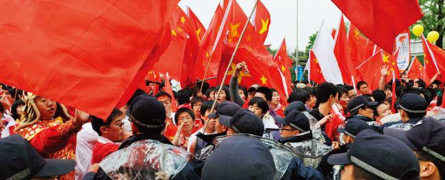 2008년 4월 27일 서울 송파구 올림픽공원에서 열린 베이징올림픽 성화 봉송 행사 과정에서 중국인들과 국내외 시민단체가 충돌해 경찰이 제지하고 있다. [뉴시스]