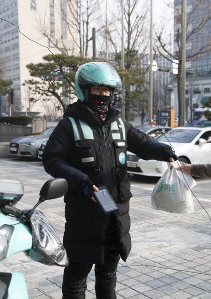 배달의민족 'B마트'에서 주문한 식료품을 배달하는 오토바이 기사. [지호영 기자]