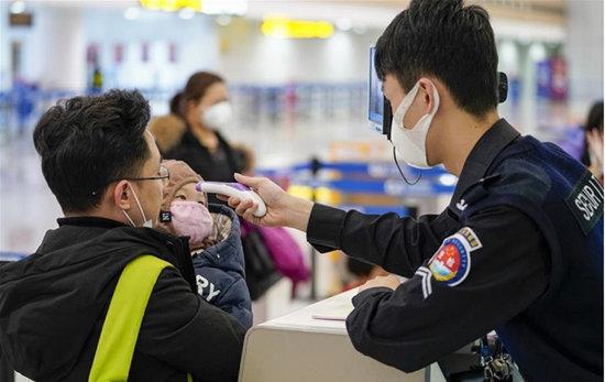 중국 보안요원이 충칭공항에서 한 어린아이의 체온을 재고 있다. [China Daily]