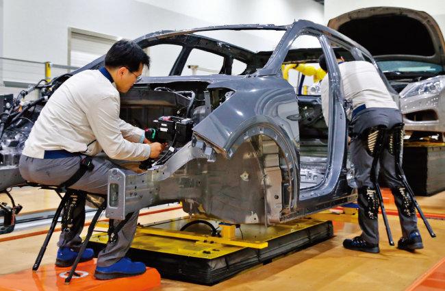 현대자동차 직원들이 자사 로보틱스팀이 개발한 착용 로봇을 입은 채 작업하고 있다. [사진 제공 · 현대자동차그룹]