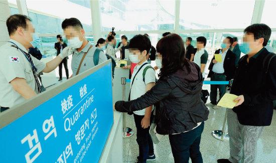 2018년 9월 10일 인천국제공항 제2터미널에 도착한 승객들을 대상으로 국립검역소 직원들이 체온을 재고 있다. [동아DB]