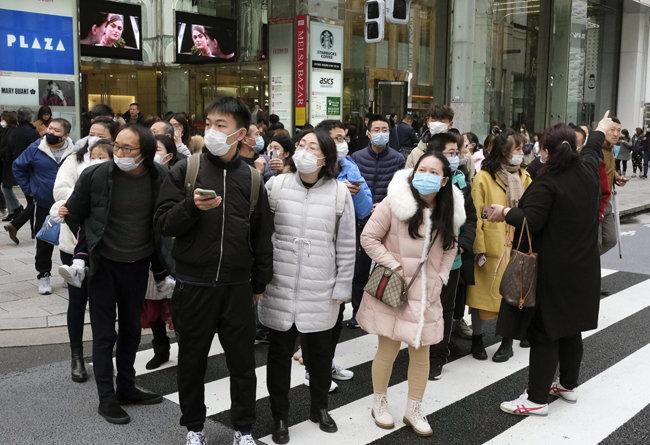 마스크를 쓴 중국 관광객들이 도쿄에서 버스를 기다리고 있다. [Japan Times]